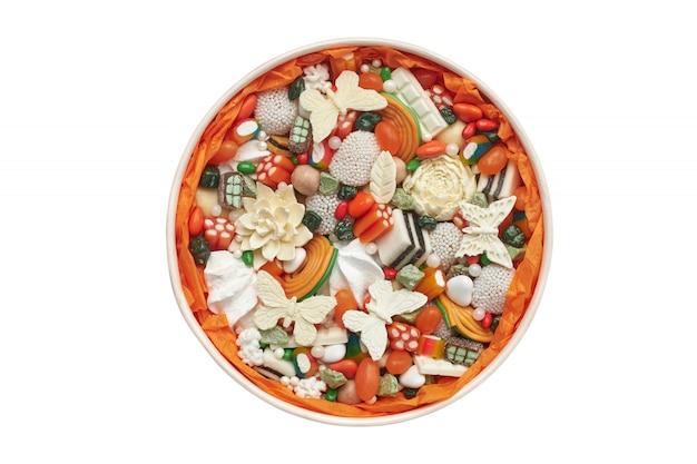 Runde schachtel gefüllt mit orangenbonbons und handgemachter schokolade isoliert auf weiß