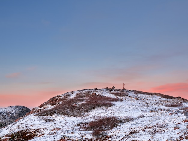 Runde schneebedeckte arktische hügel, minimalistische polarlandschaft mit einem holzkreuz auf dem berg. kola halbinsel.