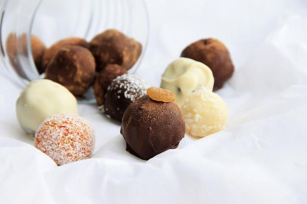 Runde schokoladen ergossen sich aus einem glas auf einer weißen serviette