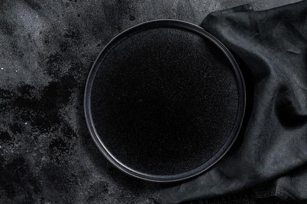 Runde schwarze platte auf strukturiertem schwarzem hintergrund