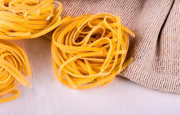 Runde spaghetti auf sackleinen und weißem tisch
