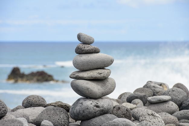 Runde steine gestapelte pyramide an der küste, balance-konzept