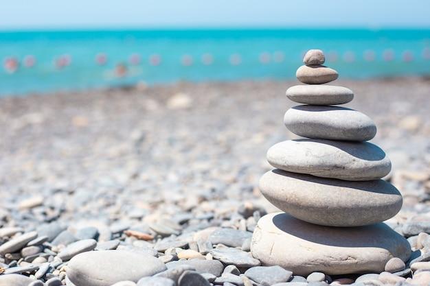 Runde steine werden an einem sonnigen tag in einer pyramide am meer übereinander gestapelt. balance-konzept. platz kopieren.