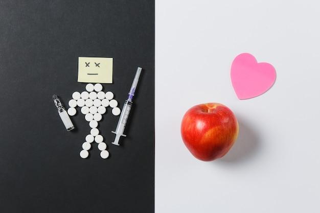 Runde tabletten der medikamente arrangierten traurigen menschen auf weißem schwarzem hintergrund