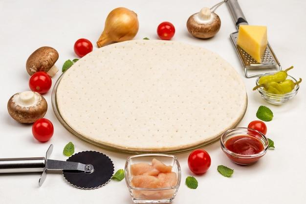 Runde teigbasis für pizza und verschiedene zutaten