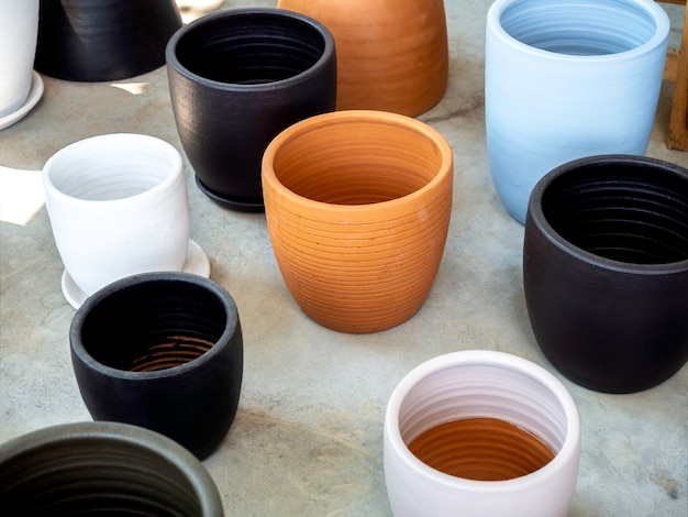 Runde terrakotta- und bunte keramiktöpfe auf betonboden angeordnet. leerer geometrischer keramikpflanzer.