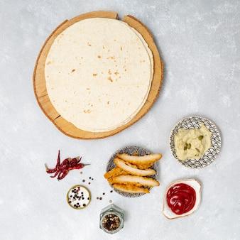 Runde tortilla mit scharfen dips neben brathähnchen