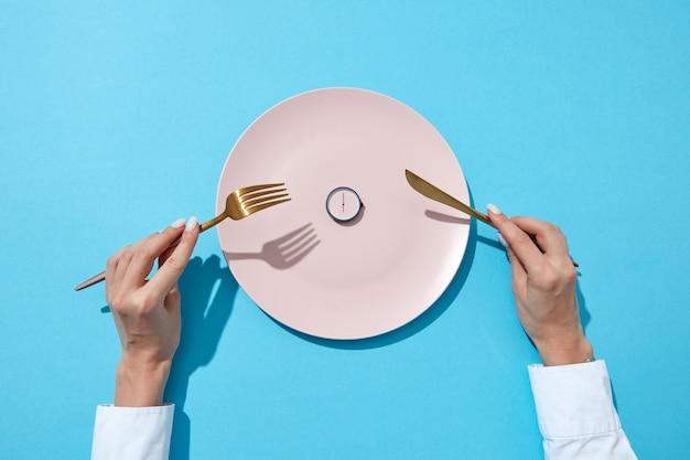 Runde uhr von sechs uhr und frauenhand mit gabel und strick in agirls händen auf einer blauen wand mit schatten. zeit zum abnehmen, esskontrolle oder diätkonzept. platz für text.