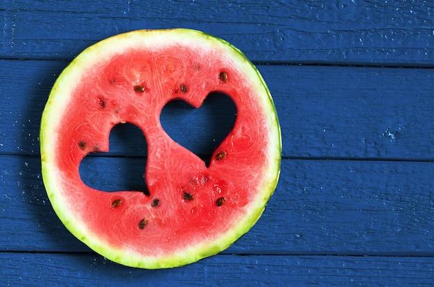 Runde wassermelonenscheibe mit schnitt in herzform auf dunkelblauem holztisch, draufsicht