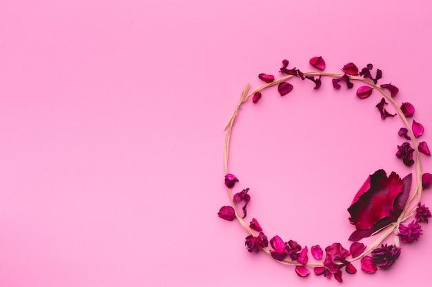 Runde zusammensetzung der getrockneten blumen auf einem rosa papierhintergrund. ein kranz aus gras und getrockneten blumen. flach legen, platz kopieren