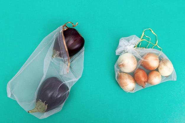 Runde zwiebeln und frische reife auberginen in öko-naturbeuteln