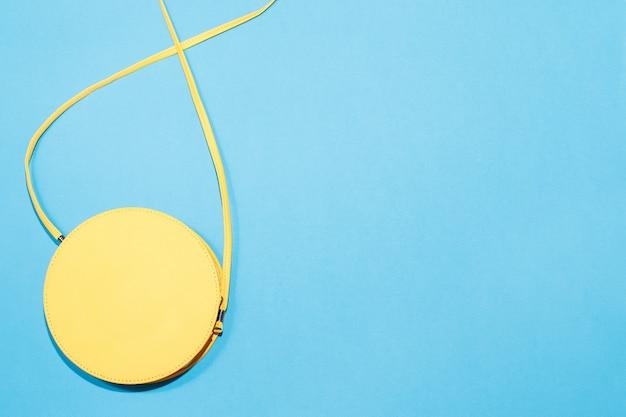 Runder gelber geldbeutel auf einem bunten blauen hintergrund