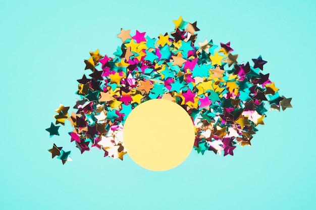 Runder gelber rahmen umgeben mit bunten sternkonfettis auf blauem hintergrund