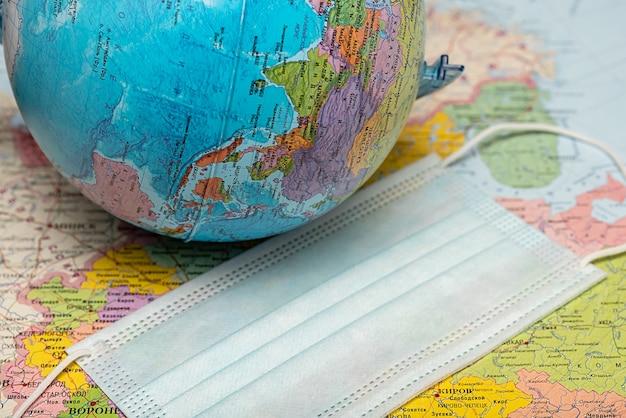 Runder globus erde auf der papierkarte der welt. auf der karte steht eine schutzmaske.