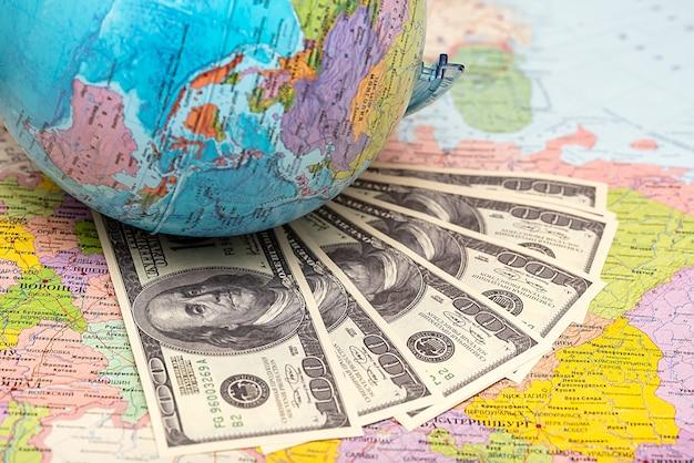 Runder globus erde auf der papierkarte der welt mit dollar