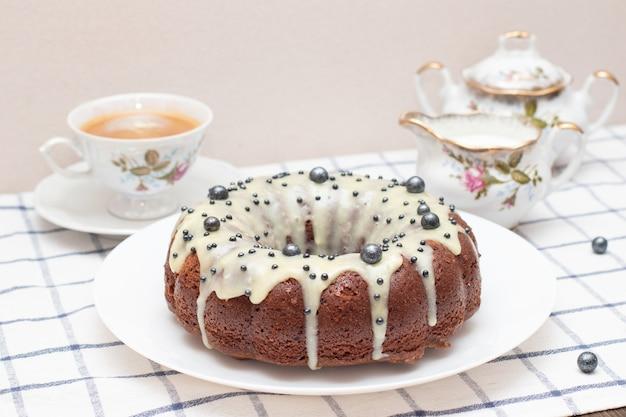 Runder hausgemachter cupcake zu ostern mit weißem zuckerguss. frisch gebackener hausgemachter protein-sahne-kuchen, teeservice, milch und eine tasse cappuccino.