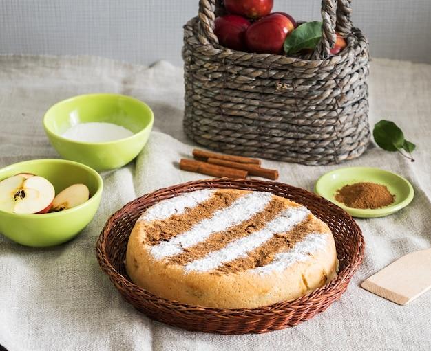 Runder hausgemachter zimt-apfelkuchen in einem korbteller mit zutaten zum kochen