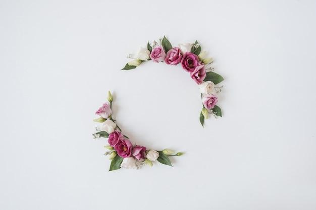 Runder kranzrahmen aus rosenblüten auf weiß
