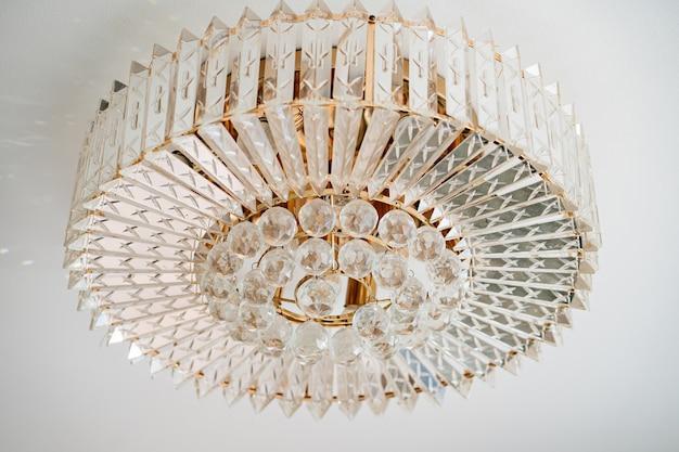 Runder kronleuchter aus glas an der weißen decke. hauptbeleuchtung. das innere eines hauses oder restaurants. innendekorelemente.