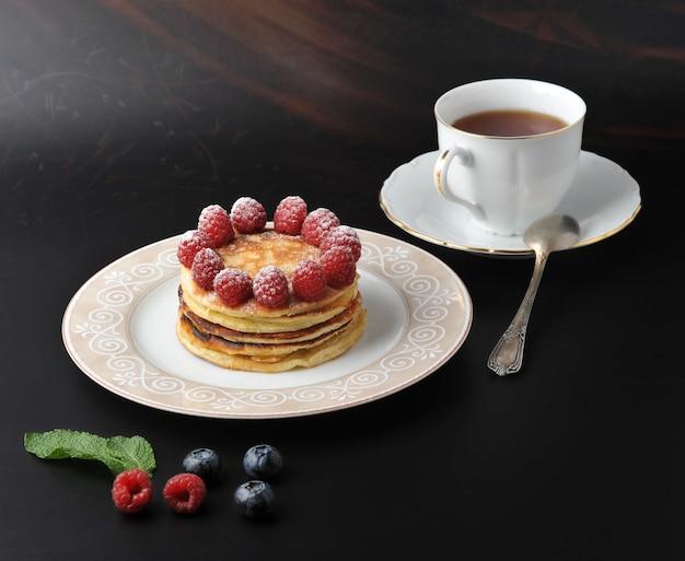 Runder kuchen mit himbeeren und tasse tee