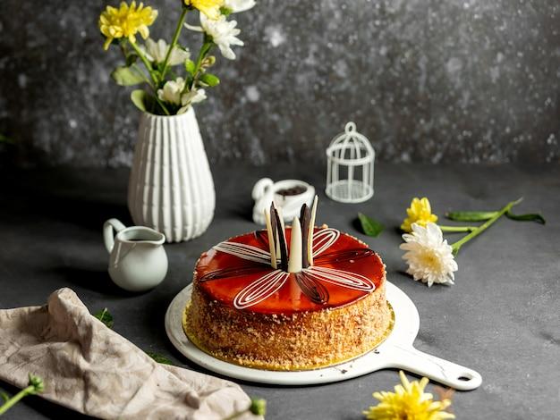 Runder kuchen mit karamellsirup weißen und dunklen pralinen dekoriert