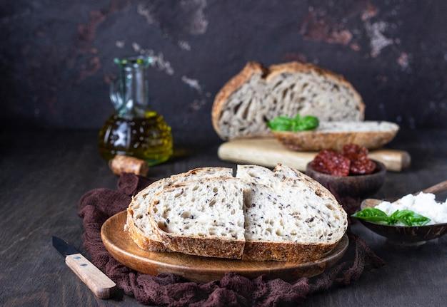 Runder laib frisch gebackenes sauerteigbrot mit ricotta, getrockneten tomaten, basilikum und olivenöl.