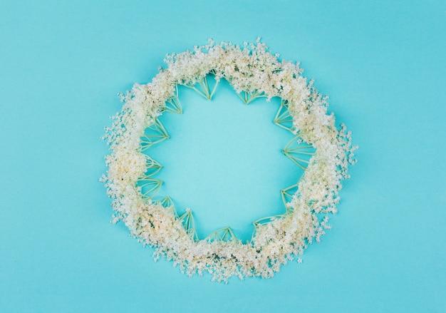 Runder mit blumenrahmen von weißen holunderbeerblumen auf blauem pastell, draufsicht
