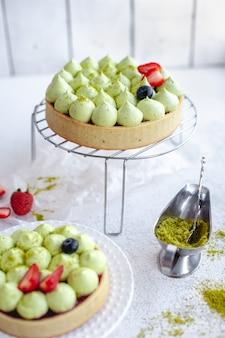 Runder mürbeteigkuchen mit grüner pistaziencreme und erdbeermarmelade