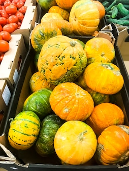 Runder orange kürbis auf supermarktregalen, verkauf.