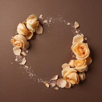 Runder rahmen aus beigen rosen auf braunem hintergrund, flach gelegen