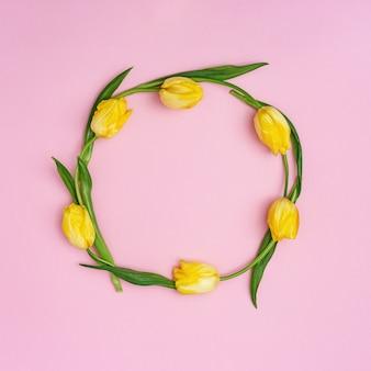 Runder rahmen aus gelb blühenden tuliten auf rosa. frühlingsblumenmuster