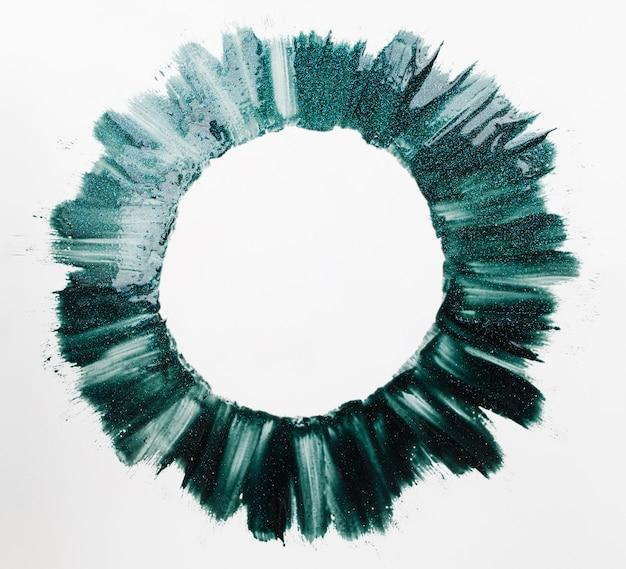 Runder rahmen aus grünem nagellack malt freien raum. heller kreis aus lack auf weißem hintergrund