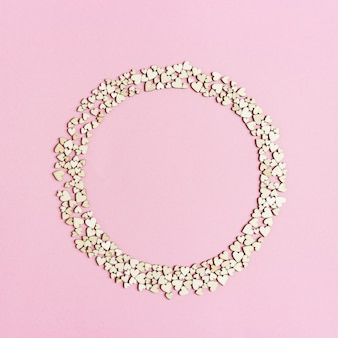 Runder rahmen aus kleinen holzherzen auf rosa papier. urlaubshintergrund