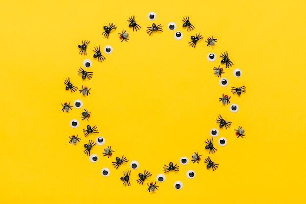 Runder rahmen aus schwarzen spinnen und fliegen, googly augen. draufsicht flat lay happy halloween kreatives konzept weihnachtskarte mock up.