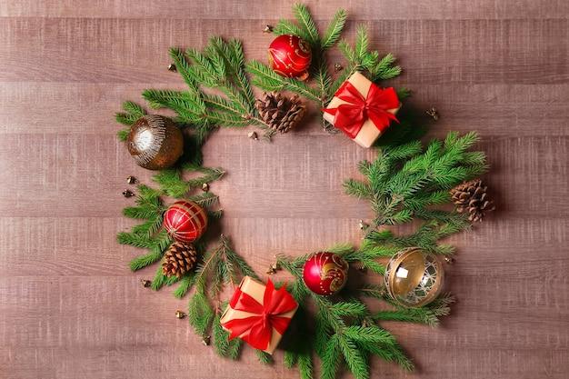 Runder rahmen aus tannenzweigen und weihnachtsdekor auf holzuntergrund