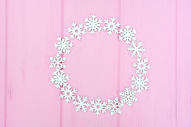 Runder rahmen des feiertags gemacht von den weihnachtsweißen schneeflocken auf rosa hölzernem