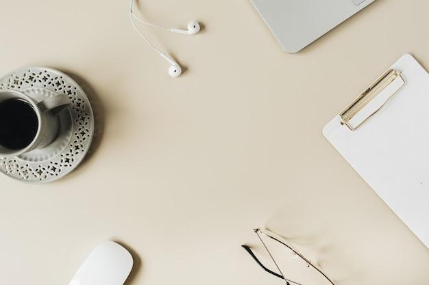 Runder rahmen leerer kopierraum home-office-schreibtisch arbeitsbereich mit laptop, zwischenablage, kopfhörern, kaffee auf beiger oberfläche. flache lage, draufsicht