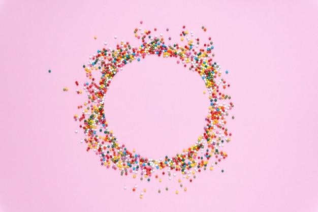 Runder rahmen von farbigen bonbons auf einem pastell farbigen hintergrund.