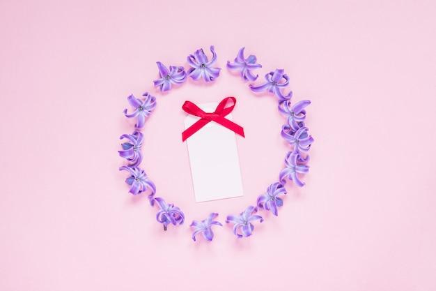 Runder rahmen von purpurroten hyazinthenpastellblumen und von leerer grußkarte mit rotem bogen auf steigungsrosahintergrund