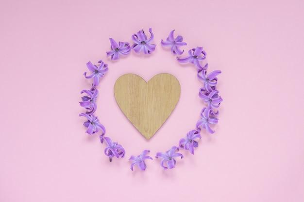 Runder rahmen von purpurroten hyezinthenpastellblumen und von hölzernem herzen auf steigungsrosa. blumenkranz. layout für feiertage gruß muttertag, geburtstag, hochzeit oder andere glückliche veranstaltung