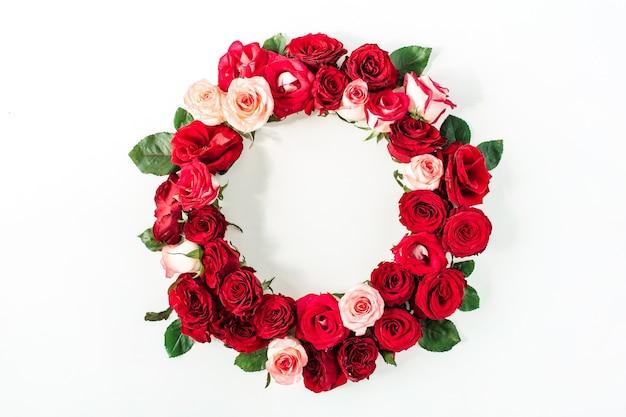 Runder rahmenrand von rosa, roten rosenblumen auf weißem hintergrund. flach liegen