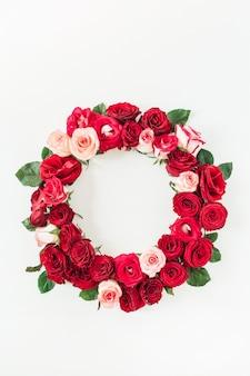 Runder rahmenrand von rosa, roten rosenblumen auf weißem hintergrund.