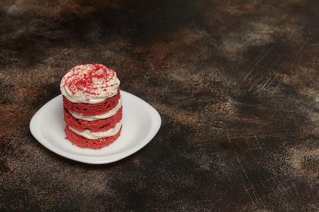 Runder roter samtkuchen mit sahne auf weißer platte