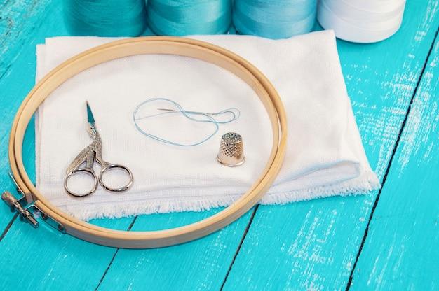Runder stickrahmen aus holz und weißer stoff zum kreuzsticken