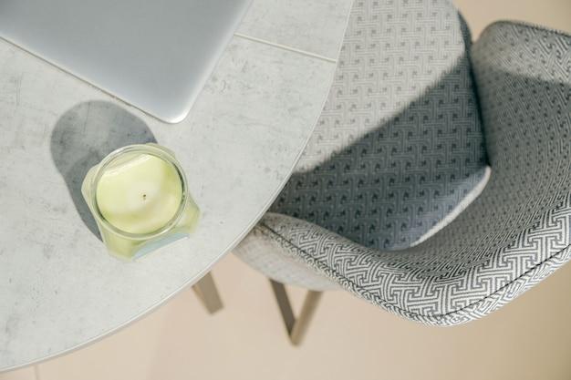 Runder tisch mit modernem sessel, aromakerze und laptop.