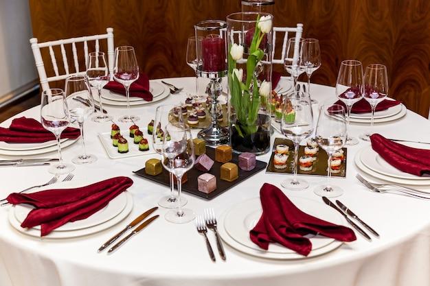 Runder tisch mit weißer tischdecke und roten servietten, besteck mit snacks für das bankett. catering, servertische für bonquet
