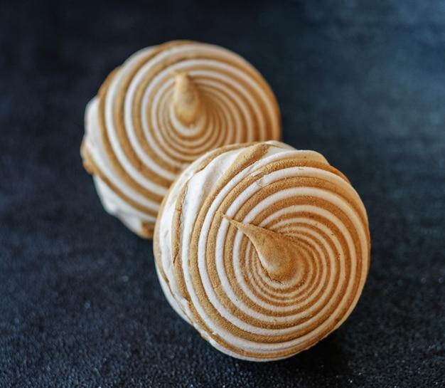 Runder weißer marshmallow mit schokoladenstreifen auf schwarzem hintergrund