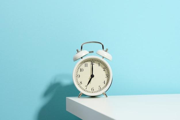 Runder weißer wecker auf dem tisch. zeit sieben uhr morgens, früh aufstehen, stunden ändern