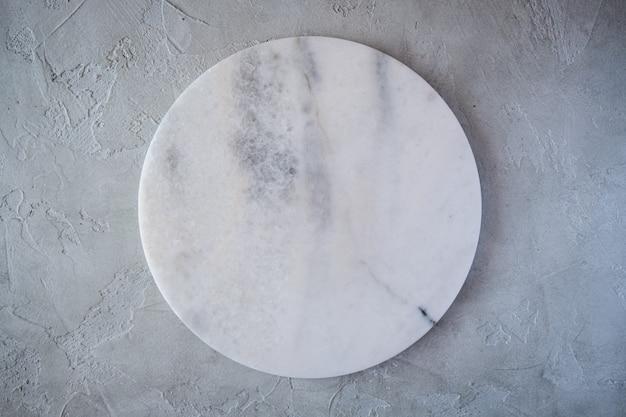 Rundes brett der weißen leeren marmorbeschaffenheit auf grauem hintergrund. draufsicht. speicherplatz kopieren.