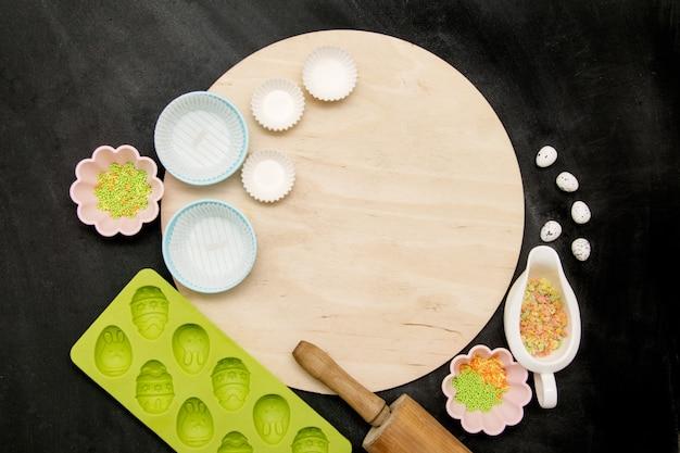 Rundes brett und zubehör für das backen von ostern-kuchen auf einem schwarzen hintergrund